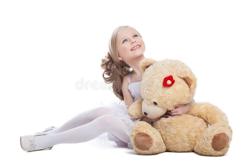 Härlig liten flicka som kramar den stora nallebjörnen arkivbilder
