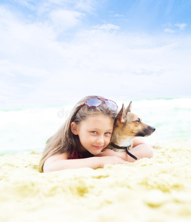 Härlig liten flicka som kramar hennes hund arkivbild