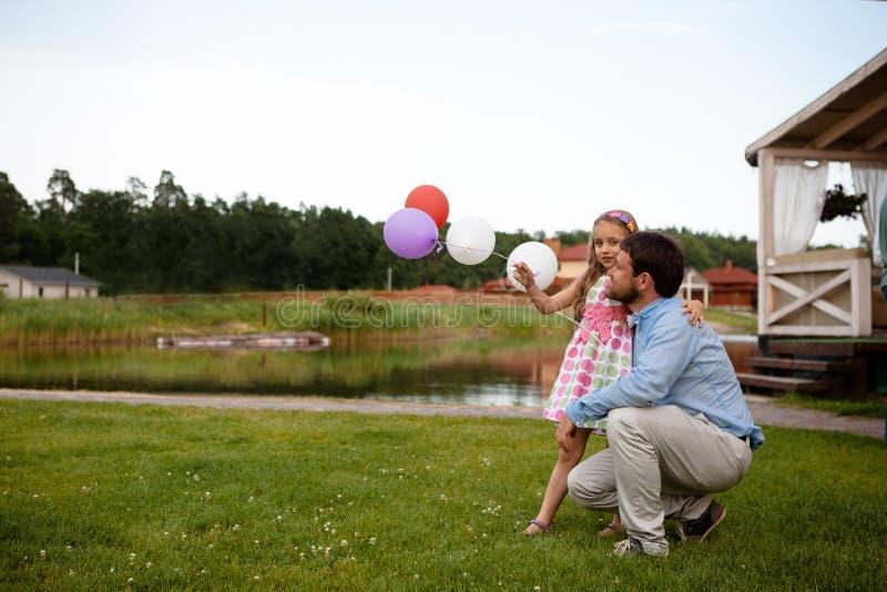Härlig liten flicka som kramar omfamna hennes fader royaltyfria foton