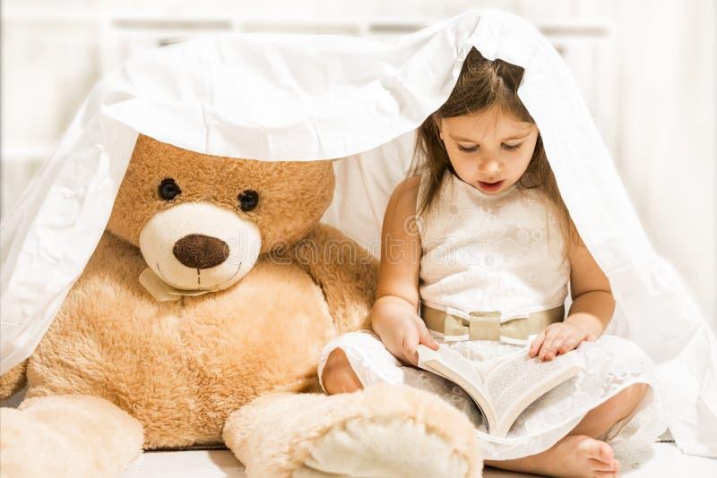 Härlig liten flicka som läser till hennes leksak för nallebjörn arkivfoton