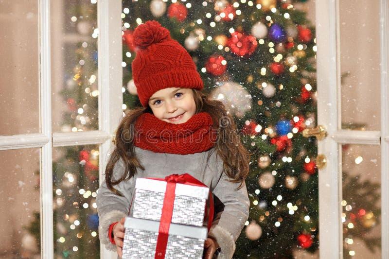 Härlig liten flicka som ler och rymmer en gåva i julst royaltyfria foton