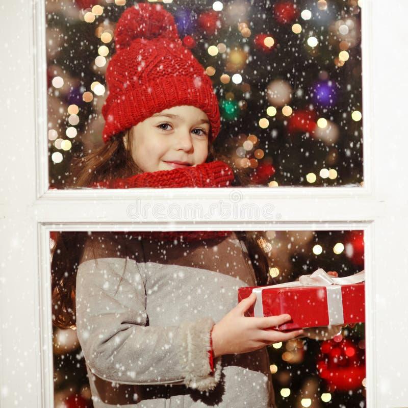 Härlig liten flicka som ler och rymmer en gåva i julst fotografering för bildbyråer