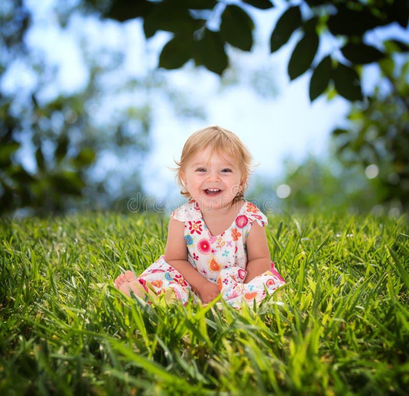 Härlig liten flicka som ler på gräset arkivbild