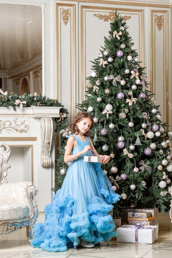 Härlig liten flicka som nära sitter till en julgran Charmig dotter i blåttklänning nytt år för gåva royaltyfria bilder