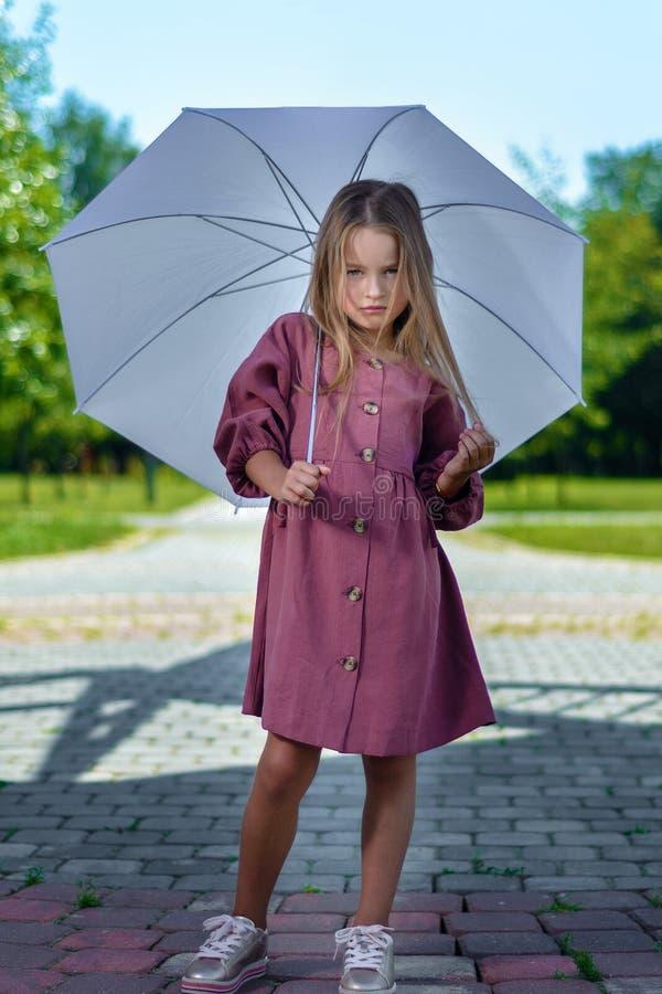 Härlig liten flicka som poserar i den burgundy klänningen under ett vitt paraply arkivfoto