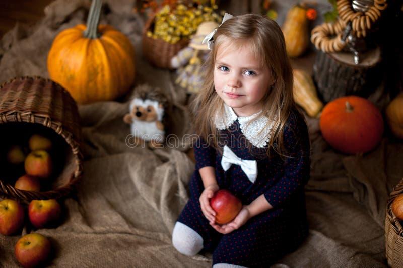 Härlig liten flicka som rymmer ett äpple royaltyfria foton