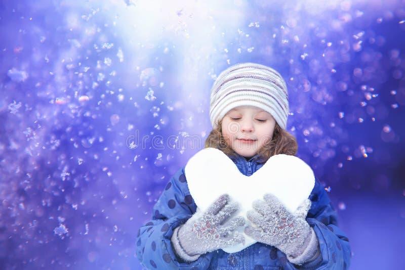 Härlig liten flicka som rymmer lyckligt en kasta snöboll royaltyfria bilder