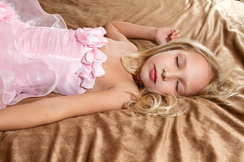 Härlig liten flicka som sover på säng royaltyfri foto