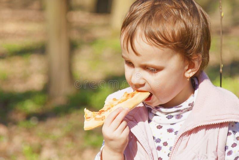 Härlig liten flicka som utomhus tycker om en läcker mat för pizza, royaltyfri bild