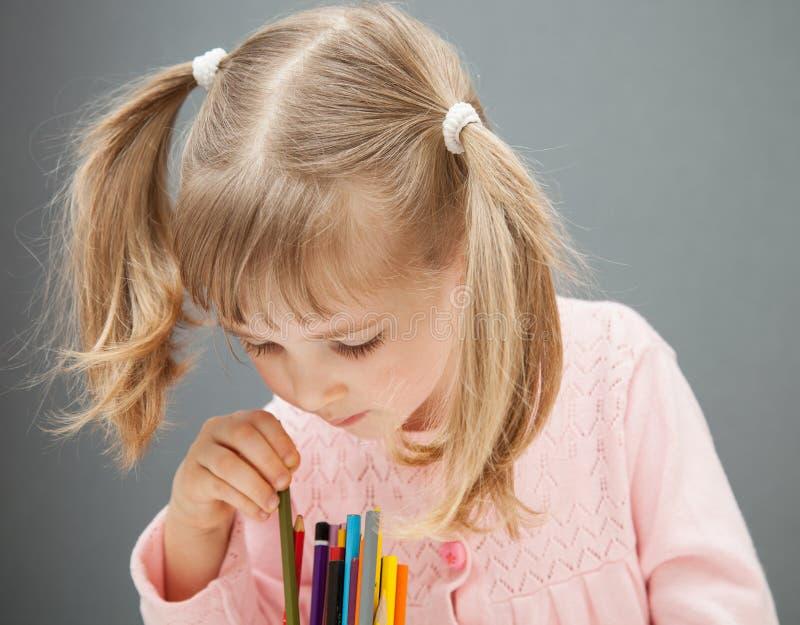 Härlig liten flicka som väljer en blyertspenna arkivbilder