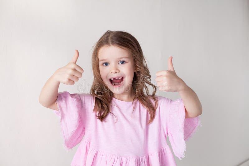Härlig liten flicka som visar tummar upp grupp royaltyfri foto