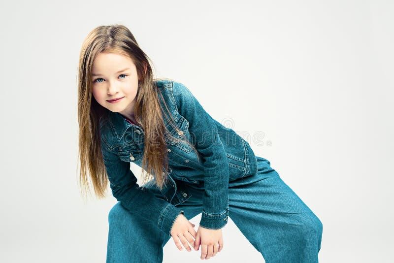 Härlig liten flickadans och posera i studion Ungemodest?ende gulligt behandla som ett barn i rörelse arkivbilder