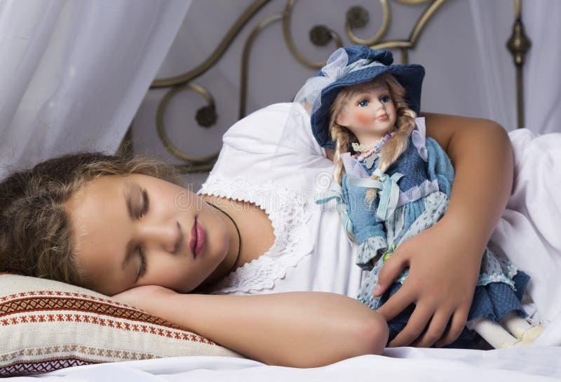 Härlig liten flickasömn i en säng och kramar henne behandla som ett barn - dockan royaltyfri bild