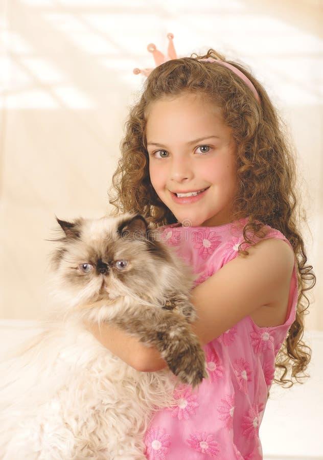 Härlig liten lockig flicka som kramar hennes katt och bär en rosa prinsessaklänning arkivbild
