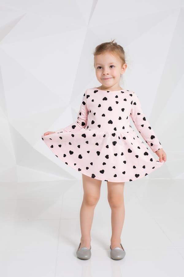 Härlig liten modemodell på vit studiobakgrund Stående av den gulliga flickan som poserar i studio royaltyfri foto