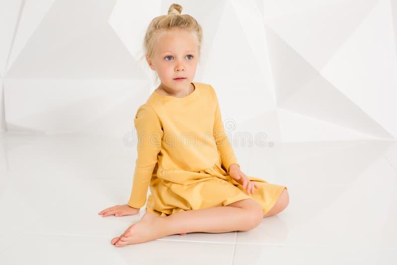 Härlig liten modemodell på vit studiobakgrund Stående av den gulliga flickan som poserar i studio royaltyfri bild
