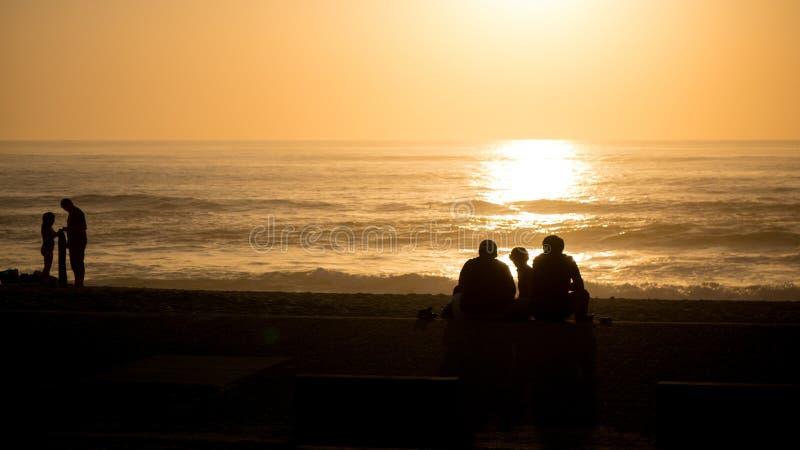 Härlig livlig strandsolnedgång med silhouetted folk över Atlantic Ocean i Vila do Conde, Porto, Portugal royaltyfri fotografi