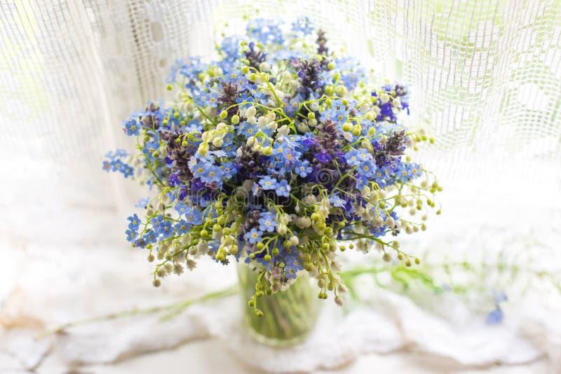 Härlig ljus blått- och vitbukett med lösa blommor på fönsterbräda i solljus Closeupfoto med bokeh royaltyfria foton