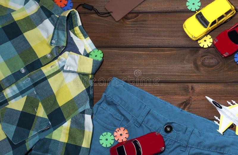 Härlig ljus kläder för en pojke på en brun bakgrund arkivfoto