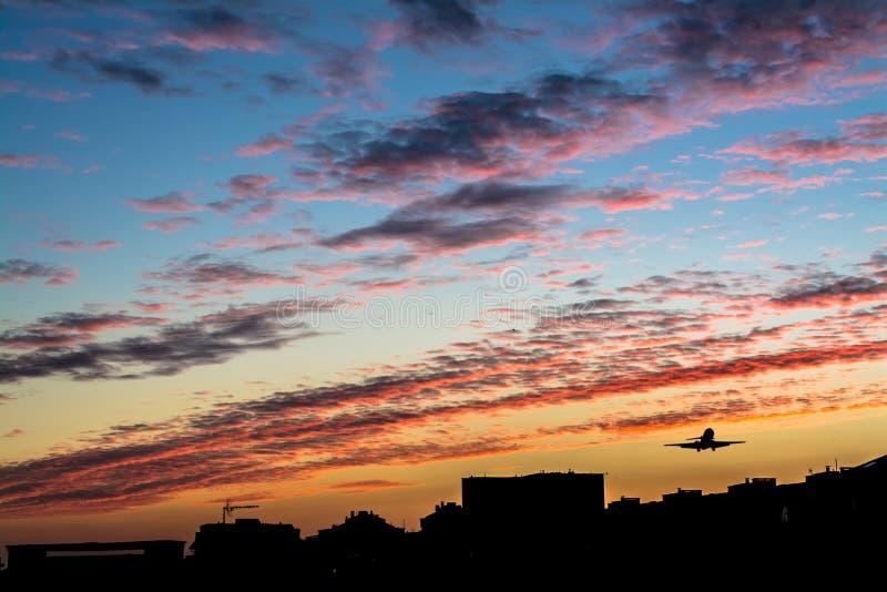 Härlig ljus solnedgång med konturn av ett flygflygplan royaltyfri bild
