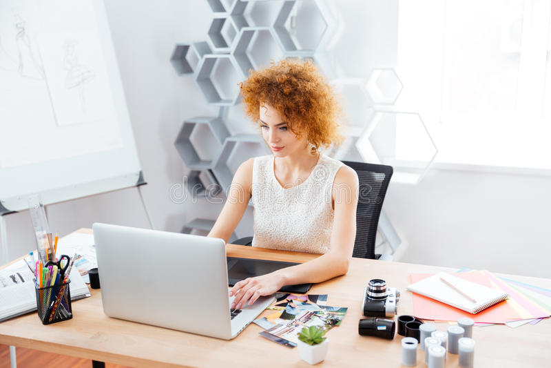 Härlig lockig fotograf för ung kvinna som använder bärbara datorn med den grafiska minnestavlan royaltyfri bild