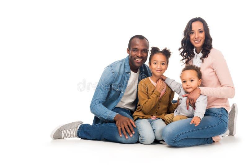 härlig lycklig afrikansk amerikanfamilj med två ungar som ler på kameran royaltyfri fotografi