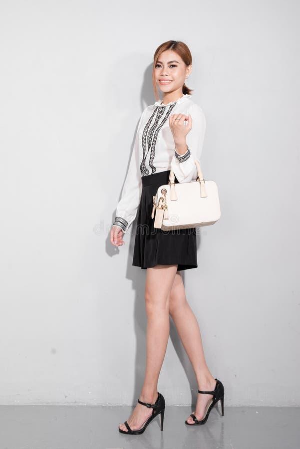 Härlig lycklig asiatisk kvinna som rymmer en påse som tillbaka går över grå färger fotografering för bildbyråer