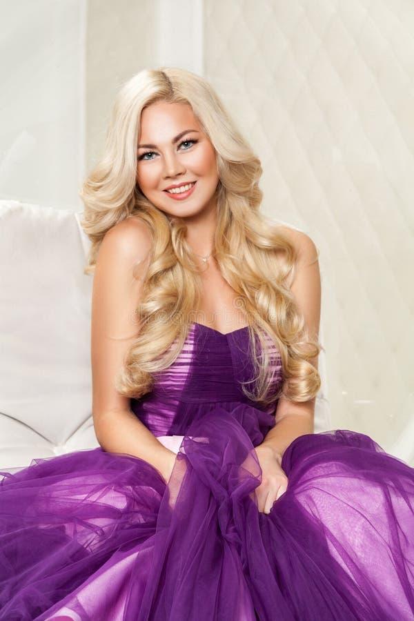 Härlig lycklig blond älskarinna i trendig purpurfärgad klänning med makeup och den långa lockiga frisyren som sitter, poserar och fotografering för bildbyråer