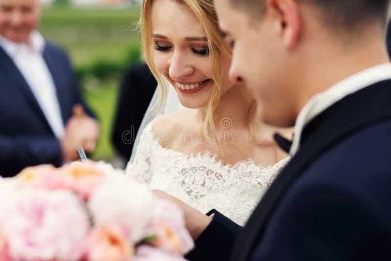 Härlig lycklig blond brud som tar löften med stiliga brudgumclo royaltyfri bild