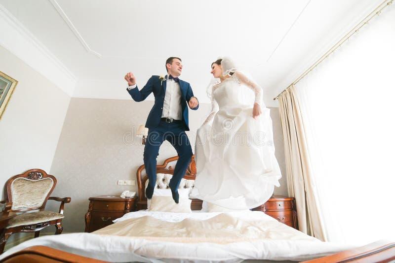 Härlig lycklig brud- och brudgumbanhoppning på sängen i rik hotellinre royaltyfria foton