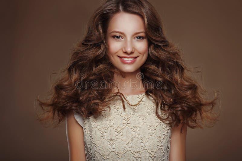Härlig lycklig brunett med långa lockiga hår fotografering för bildbyråer