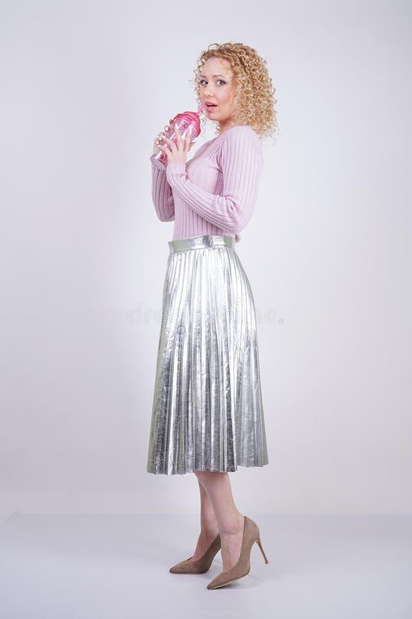 Härlig lycklig caucasian kvinna med lockiga ställningar för blont hår i en tunn rosa stucken tröja och en metallisk silver plisse fotografering för bildbyråer