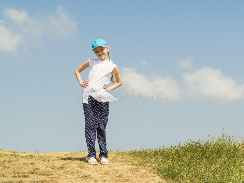 Härlig lycklig flicka i en blå baseballmössa överst av en kulle på en bakgrund av blå himmel med moln royaltyfri fotografi