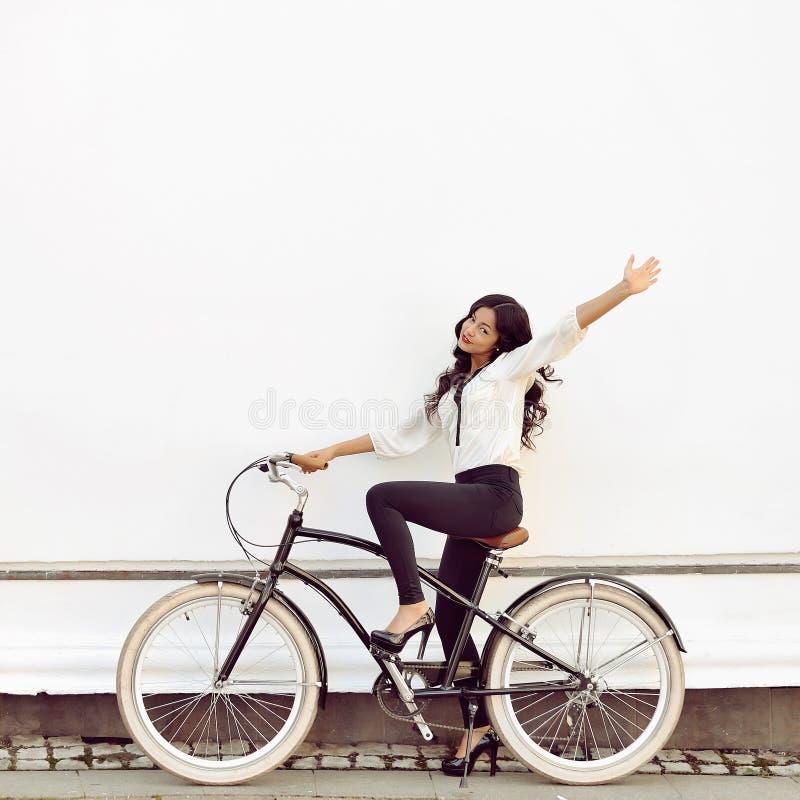 Härlig lycklig flicka på en tappningcykel arkivbild