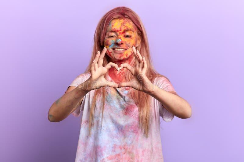 Härlig lycklig flicka som gör en hjärta från fingrar fotografering för bildbyråer