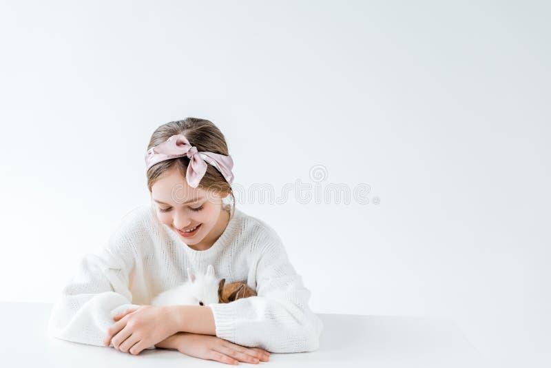 Härlig lycklig flicka som spelar med förtjusande päls- kaniner fotografering för bildbyråer