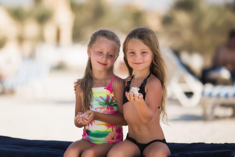 Härlig lycklig flicka två på stranden nära havet med skal i deras händer royaltyfri foto