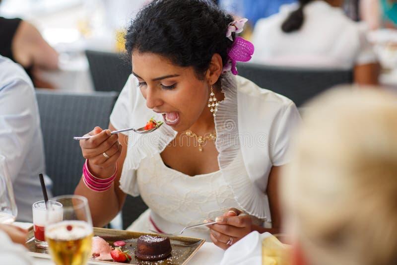 Härlig lycklig indisk brud som äter på bröllopmatställe. arkivbild