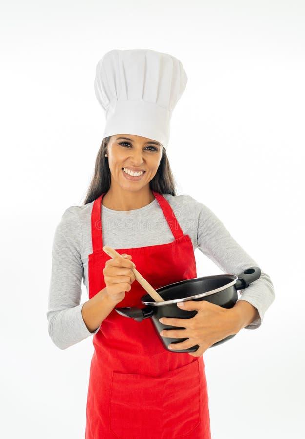 Härlig lycklig kock för ung kvinna som rymmer en träsked och en kruka med det röda förklädet och vithatten royaltyfria foton