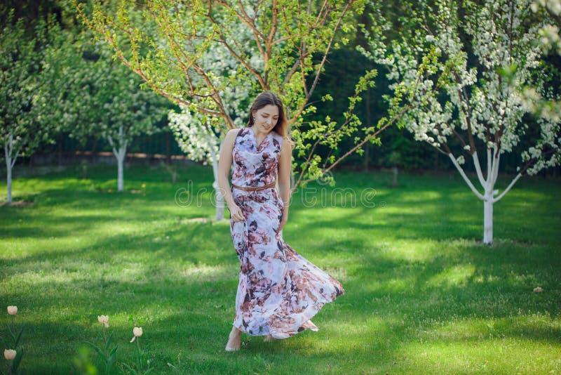 Härlig lycklig kvinna för stående som tycker om lukten i en blommande trädgård för blomningvår Ljus och trendig le flicka nära bl arkivbilder