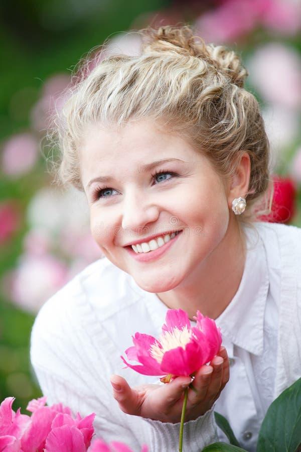 Härlig lycklig kvinna i blommaträdgård royaltyfria foton