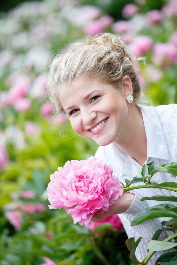 Härlig lycklig kvinna i blommaträdgård fotografering för bildbyråer