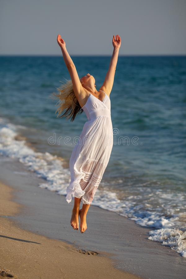 Härlig lycklig kvinna i den vita klänningen som hoppar upp på stranden på en solig dag royaltyfria foton