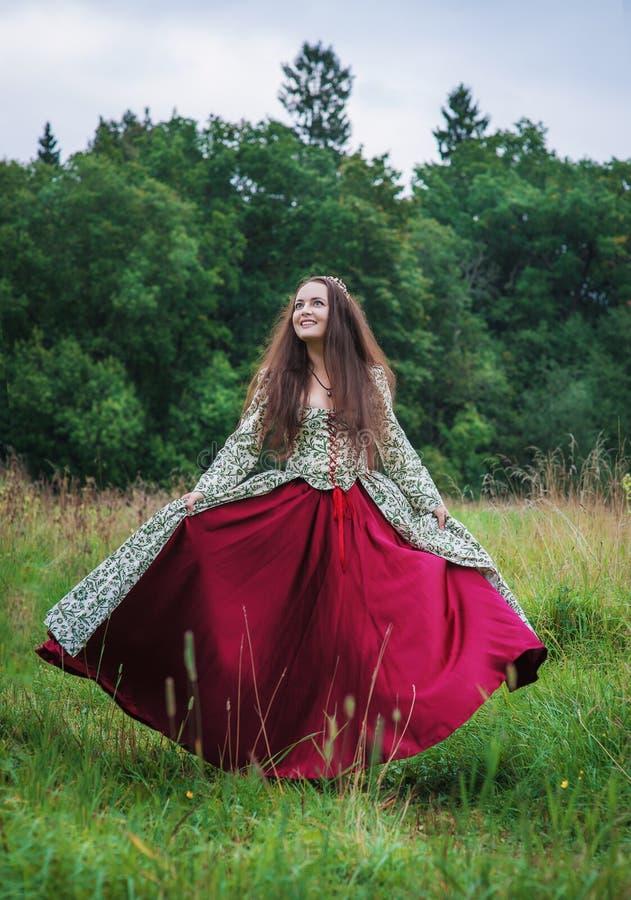 H?rlig lycklig kvinna i medeltida den utomhus- kl?nningdansen arkivfoto