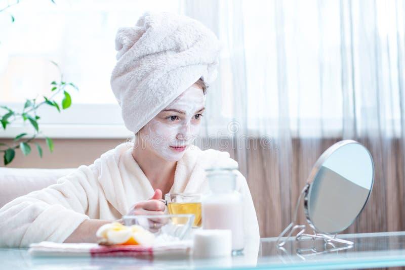 Härlig lycklig kvinna med den naturliga kosmetiska maskeringen på hennes framsida Hudomsorg och Spa behandlingar arkivbild