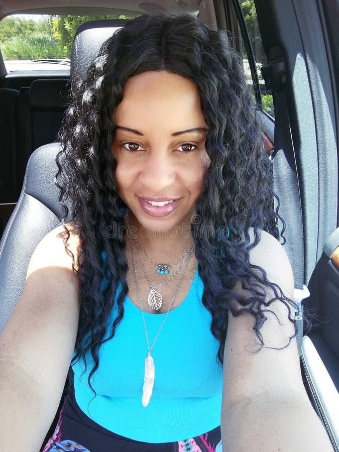 Härlig lycklig kvinna med svart krabbt hår i bilfotografi som bär en blå överkant med tillbehör fotografering för bildbyråer