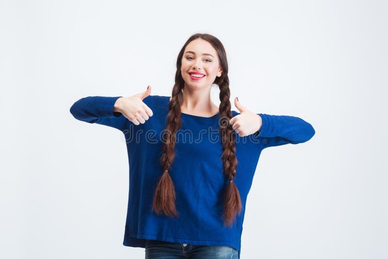 Härlig lycklig kvinna med två flätade trådar som visar upp tummar royaltyfri fotografi