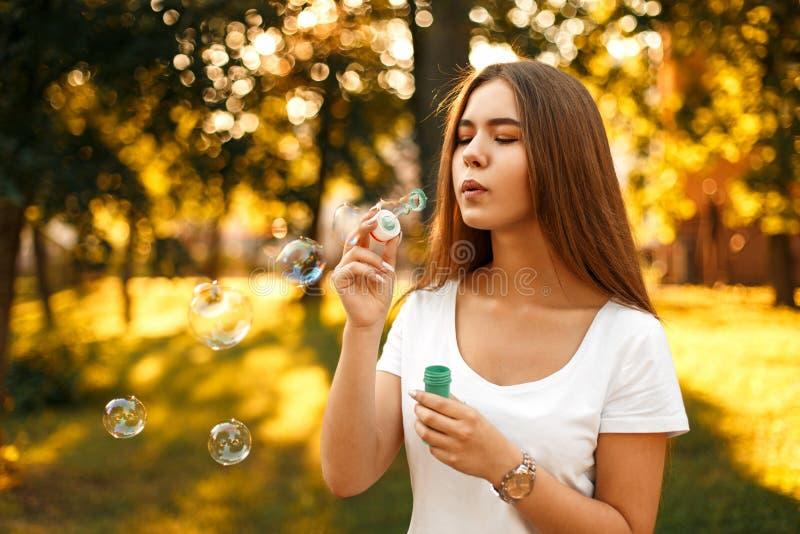 Härlig lycklig kvinna som blåser såpbubblor på en solig sommardag arkivfoton
