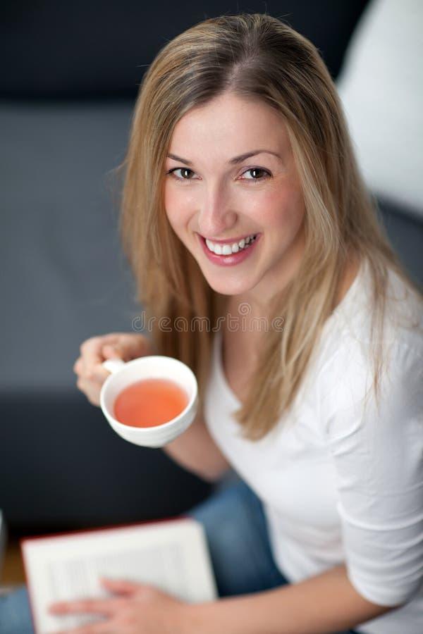Härlig lycklig kvinna som dricker te fotografering för bildbyråer