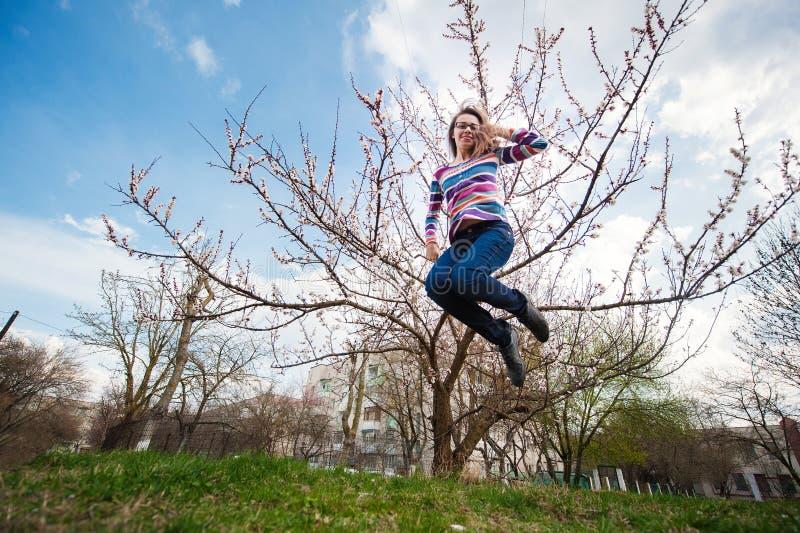 Härlig lycklig kvinnabanhoppning i våren som blomstrar trädgården royaltyfri foto